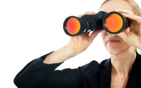Businesswoman looking through binoculars against a white background Stock Photo - 13217770