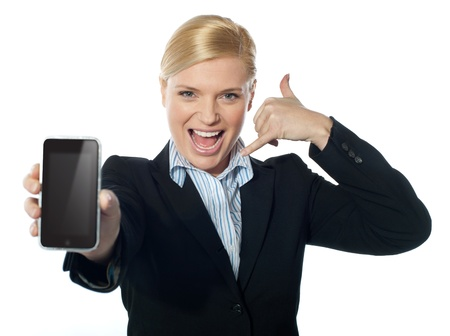 saleswoman: Saleswoman displaying smartphone to camera, based on touch-pad technology Stock Photo