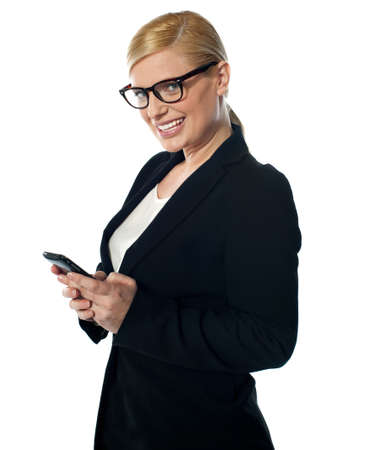 Female business executive texting on phone in front of camera photo