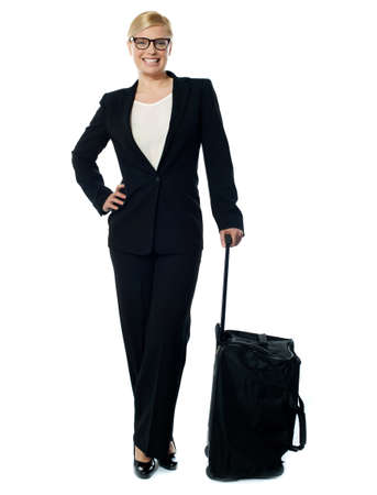 Corporate person carrying trolley bag and posing with arms on her waist Stock Photo - 13217777