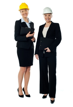 Two charismatic female architects looking at camera, holding files photo