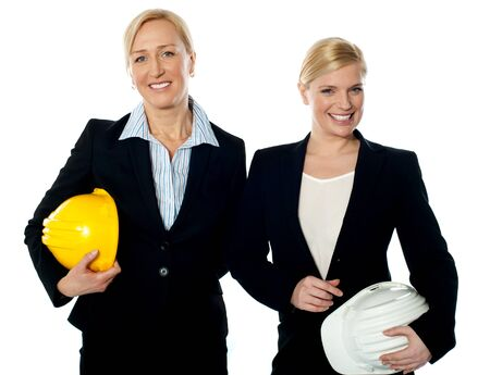 Young female architects holding hard-hats and posing against white background photo