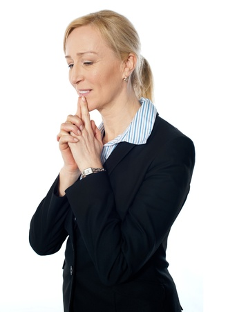downwards: Senior corporate woman posing with fingers on her lips, looking downwards Stock Photo