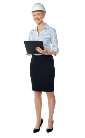 Successful senior female architect posing with document against white background Stock Photo - 13217756