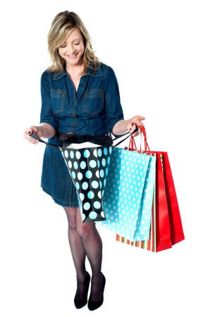 Fashionable woman looking into shopping bags, isolated on white background Stock Photo - 13236743