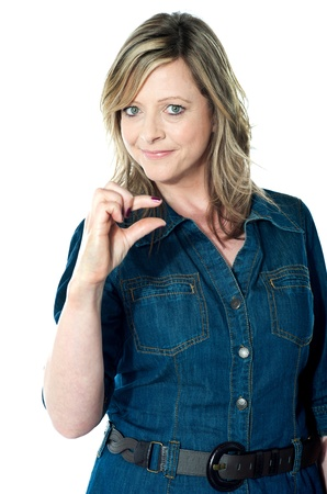 Female indicating little bit gesture against white background photo