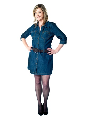 Beautiful woman posing with arms on her waist in trendy blue outfit photo