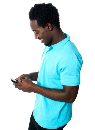 cool boy: African boy busy messaging and smiling while reading message Stock Photo