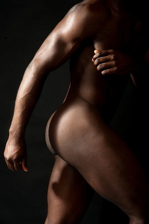 naked abs: Cropped image of a nude african man over black background