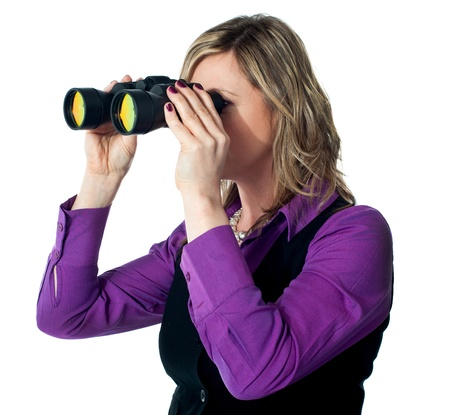 Businesswoman looking through binoculars against a white background Stock Photo - 13236741