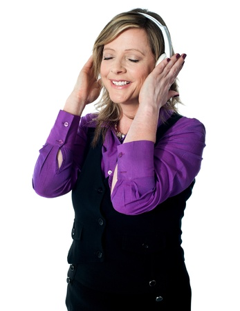 Senior lady listening to music with closed eyes, lost deeply in it photo
