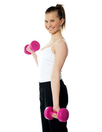 Strong teenager working out with dumbbells. Shot in studio on a white background Stock Photo - 13324527