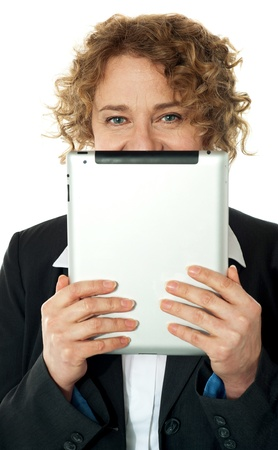 i pad: Corporate lady hiding her face with ipad, smiling at camera
