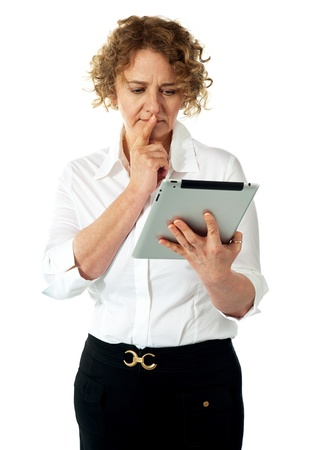 Businesswoman looking at tablet and thinking deep. Lost in thoughts Stock Photo - 13324840