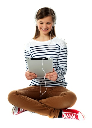 Girl watching video on her tablet with headphones attached Stock Photo - 13324852