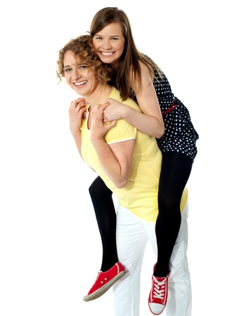 Teenage girl piggybacks her mother, studio shot photo