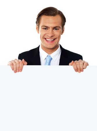Smiling businessman holding a blank poster against white background Stock Photo - 13373345