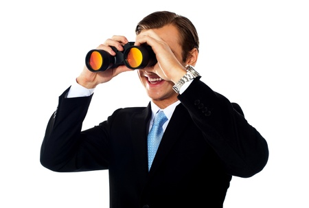 Business professional looking through binoculars  Isolated on white photo