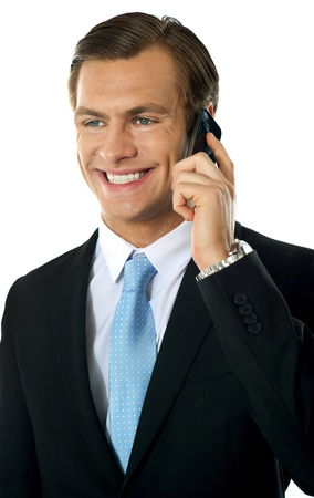 Young businessman talking on mobile phone looking away and smiling photo