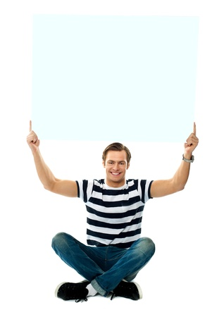 Seated man showing blank signboard against white background Stock Photo - 13373351