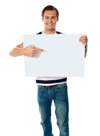 Portrait of young man pointing at blank signboard  Isolated on white photo