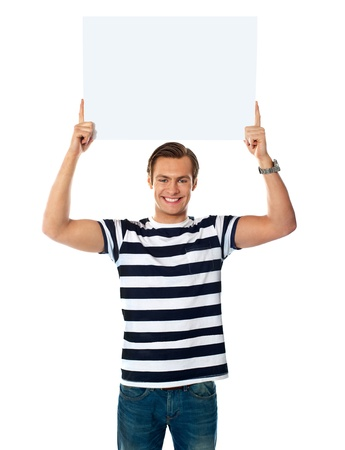 blank banner: Confident young man showing blank billborad over his head