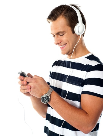 Male teenager with mp3 player and earbuds listen to music  Surfing playlist photo