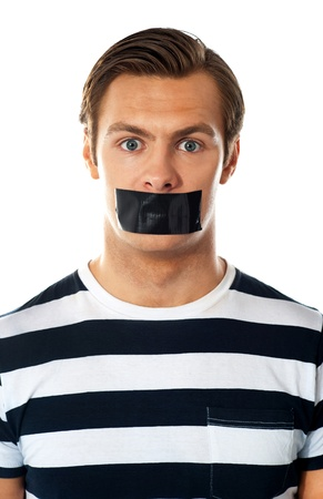 Closeup of a worried man  Mouth covered with duct tape photo