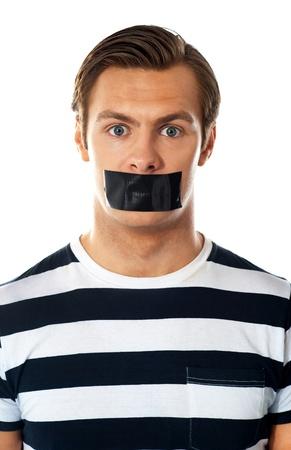 hombre preocupado: Primer plano de un hombre preocupado la boca cubierta con cinta adhesiva