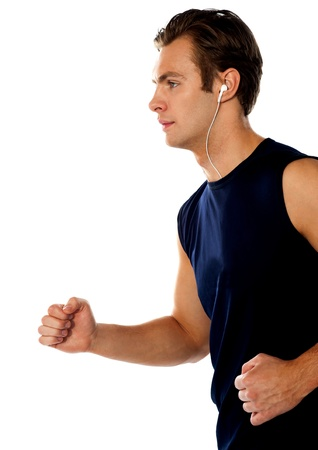 Fit athlete enjoying music in a jogging posture wearing sporty outfit photo