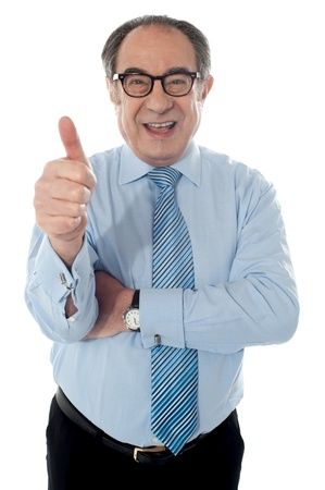 positive positivity: Matured businessman gesturing thumbs-up sign at you isolated on white Stock Photo