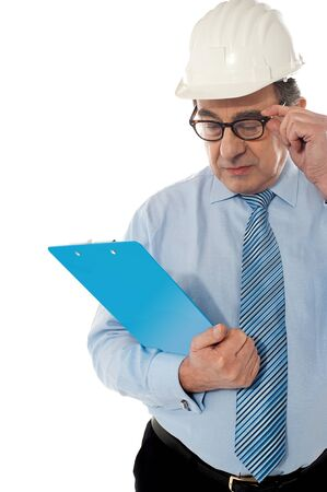 Experienced achitect in hardhat studying files  Isolated on white Stock Photo - 13522298