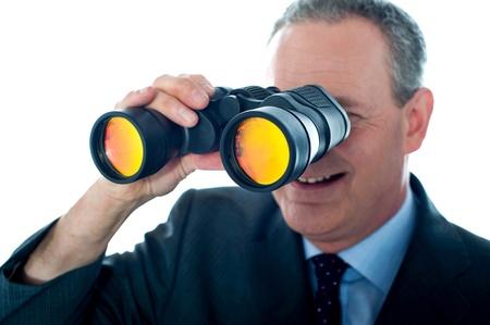 Senior man observing through binoculars isolated over white background photo