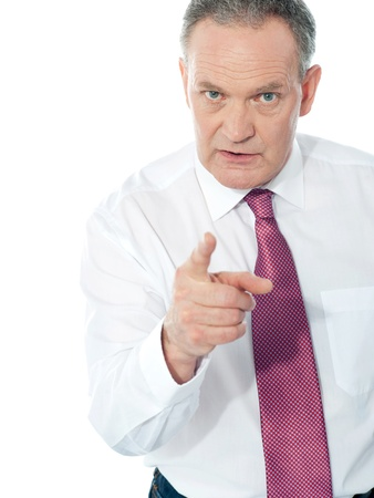 angry boss: Portrait of an angry middle aged businessman in suit pointing at you isolated over white background Stock Photo