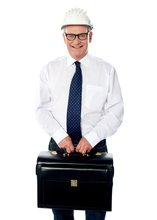 Handsome senior builder holding briefcase isolated against white photo