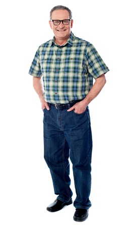 Joyful senior man posing casually with hands in pocket isolated on white photo