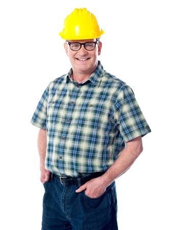 Smiling matured architect posing with hands in pocket. Wearning hard-hat photo