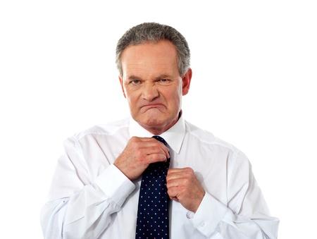 tahriş: Serious businessman adjusting his tie, irritation on his face