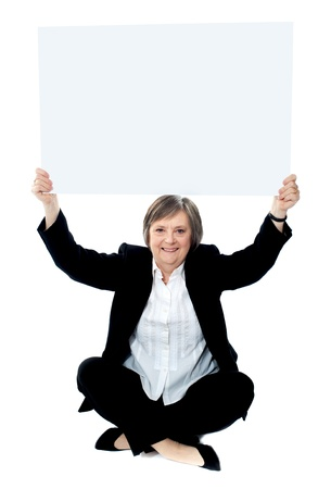 Seated businesswoman holding blank whiteboard over her head Stock Photo - 13737835