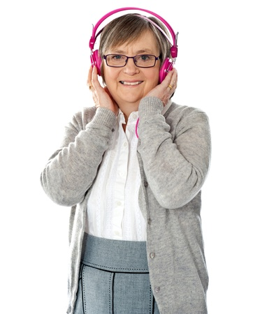 Attractive old lady wearing headphones listening music photo