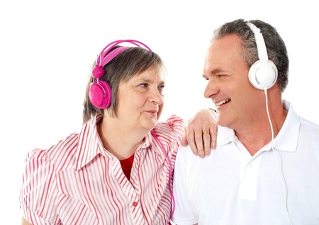 Romantic senior couple enjoying music together. Wife resting her hand on shoulders of her man photo