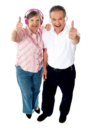 Thumbs-up couple tuned into music, isolated over white photo