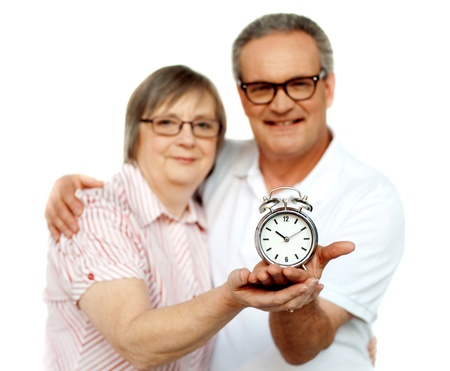 Aged couple with alarm clock on palm isolated over white photo