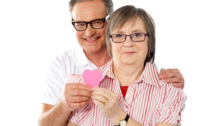 Portrait of a matured smiling couple holding paper heart. Showing to camera photo