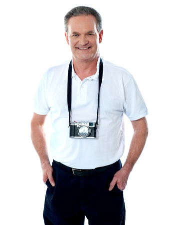 Mature cameraman posing smartly with hands in pocket  Camera around his neck photo