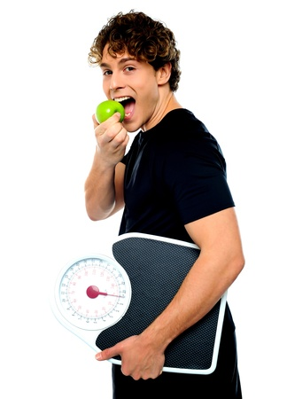 Smart boy eating green apple with scale in his other hand photo