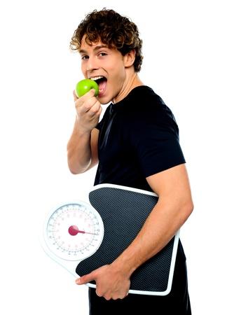 Intelligente Junge isst grünen Apfel mit Skala in der anderen Hand