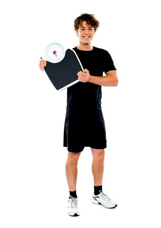Handsome fit man holding weight machine over white background background photo