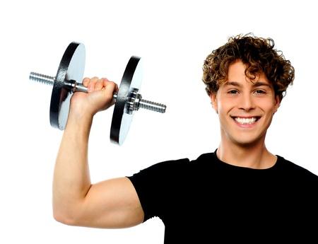levantando pesas: Potente joven musculoso levantamiento de pesas, sonriendo plantean Foto de archivo