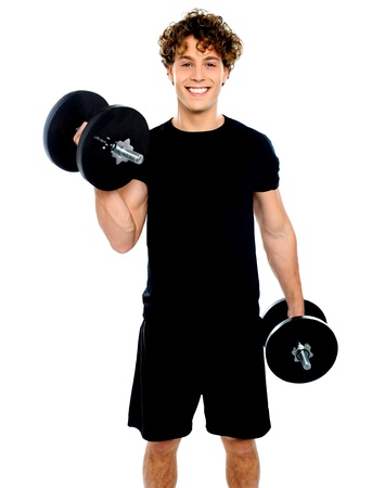 Muscular man doing exercise using bumbbells against white background